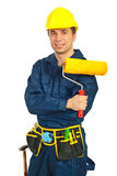 Happy worker man holding paint roller. Against white background Stock Photography