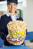 Happy Worker Offering Popcorn At Cinema Concession Stock Images