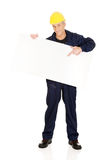 Happy worker presenting empty banner. Happy mature worker presenting empty banner Royalty Free Stock Photos