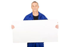 Happy worker presenting empty banner. Happy mature repairman presenting empty banner Stock Photography