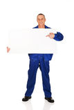 Happy worker presenting empty banner. Happy mature repairman presenting empty banner Royalty Free Stock Photos