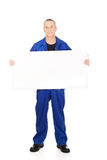 Happy worker presenting empty banner. Happy mature repairman presenting empty banner Stock Image