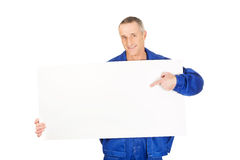 Happy worker presenting empty banner. Happy mature repairman presenting empty banner Stock Photo