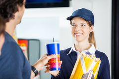 Happy Worker Selling Popcorn And Drink To Man At Stock Photo