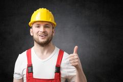 Happy worker showing thumbs up sign. Smiling worker with yellow hard hat showing thumbs up sign Stock Photos
