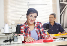 Happy Worker Sitting At Workbench In Sewing Factory. Portrait of happy female worker sitting at workbench with colleague working in background at sewing factory Stock Photo