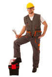 Happy Worker standing on Toolkit And holding  Wrench Over White Royalty Free Stock Images