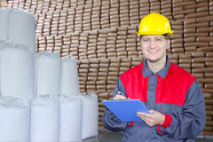 Happy Worker in Warehouse. Writing on clipboard Royalty Free Stock Photo