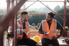 Happy Workers In Construction Site During Lunch Break. People working in construction site. Men at work in new housing project. Team of happy workers laughing stock image