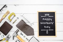 Happy Workers` Day background concept. Flat lay of construction blue collar handy tools and white collar`s accessories over wood. En background with black royalty free stock image