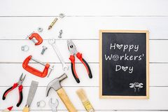 Happy Workers` Day background concept. Flat lay of construction handy tools with black chalkboard with Happy Workers` Day text. Over white wooden floor royalty free stock images