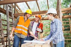 Happy Workers Discussing Over Blueprint At Site. Happy male and female workers discussing over blueprint in incomplete wooden cabin at site Stock Photos