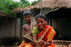 Happy working. A tribal woman making handicraft with her child Royalty Free Stock Photography