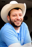 Happy Working Cowboy. Closeup of a happy smiling unshaven working cowboy with western hat. Shallow depth of field Stock Photo