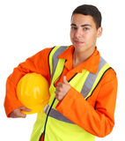 Happy workman. A workman with a thumbs up sign holding his hard hat Royalty Free Stock Image