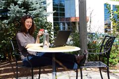 Happy workplace. Woman relaxing as she works outside the office Royalty Free Stock Images
