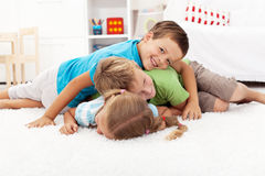 Happy wrestling kids in a pile Stock Images