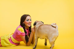 Happy wwoung woman in doll dress feed a small dog Royalty Free Stock Images