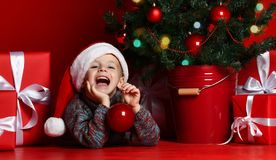 Happy xmas and New Year. Portrait of child in Santa red hat waiting for Christmas gifts. stock images