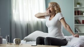 Happy yawning woman sitting on bed, weekend morning time, health an harmony stock images