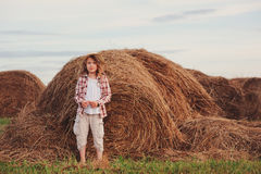 Happy 7 years old child girl in country style plaid shirt and hat relaxing on summer field with hay stacks Stock Photos