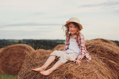 Happy 7 years old child girl in country style plaid shirt and hat relaxing on summer field with hay stacks Stock Photo