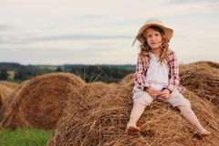 Happy 7 years old child girl in country style plaid shirt and hat relaxing on summer field with hay stacks Stock Image