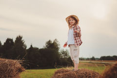 Happy 7 years old child girl in country style plaid shirt and hat relaxing on summer field with hay stacks Royalty Free Stock Photo