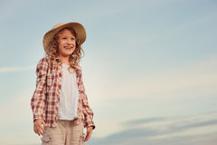 Happy 7 years old child girl in country style plaid shirt and hat relaxing on summer field with hay stacks Royalty Free Stock Images