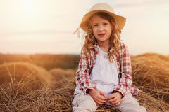 Happy 7 years old child girl in country style plaid shirt and hat relaxing on summer field with hay stacks Royalty Free Stock Photos