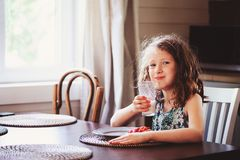 Happy 8 years old child girl having breakfast in country kitche Royalty Free Stock Photos
