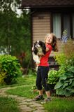 Happy 8 years old child girl playing with her spaniel dog outdoor Royalty Free Stock Photography