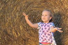 A happy 3 years old girl having fun with hay on a farm Stock Photography