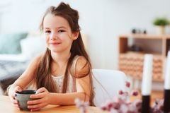 Happy 5 years old kid girl having breakfast at home in the morning. Sitting at table with cup with tea or hot cocoa, healthy life concept in modern Royalty Free Stock Photography
