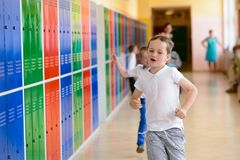 Happy 7 years old schoolboy running out of school. Royalty Free Stock Images