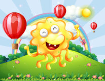 A happy yellow monster at the hilltop with a rainbow and floatin Stock Images