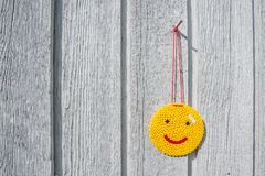 Happy yellow smiley hanging on a wall Royalty Free Stock Photography