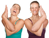 Happy Yoga Women. Two laughing women performing entwined namaskar over white background Royalty Free Stock Photography