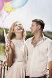 Happy yong couple with ballons. Holiday and love concept. Happy yong couple with ballons embracing and smiling Royalty Free Stock Photos