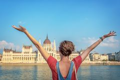 Happy youg girl raising arms in from of Budapest parliament Hungary royalty free stock images