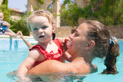 Happy young active mother and curly little baby having fun in a swimming pool Royalty Free Stock Image