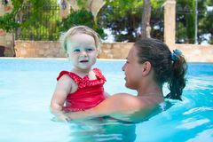 Happy young active mother and  curly little baby having fun in a swimming pool Royalty Free Stock Photography
