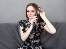 Happy young adorable woman in long dress on grey sofa holding hair styler up at home against grey wall stock image