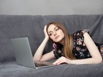 Happy young adorable woman in long dress lies on grey sofa with laptop at home against grey wall stock photo
