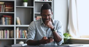 Happy young adult African man using smartphone in home office