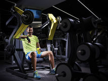Happy young adult bodybuilder doing weight lifting in gym. Royalty Free Stock Image