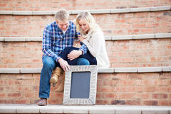 Happy young adult couple looking down at your text, focus on sig Stock Photo