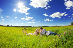 Happy young adult couple in love on the field. Two,  man and wom. Happy young adult couple in love on the field. Two,  men and women smiling and resting on the Royalty Free Stock Images