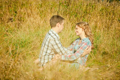 Happy young adult couple in love on the field. Two,  man and wom. Happy young adult couple in love on the field. Two,  men and women smiling and resting on the Royalty Free Stock Photography