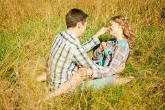 Happy young adult couple in love on the field. Two,  man and wom. Happy young adult couple in love on the field. Two,  men and women smiling and resting on the Stock Image